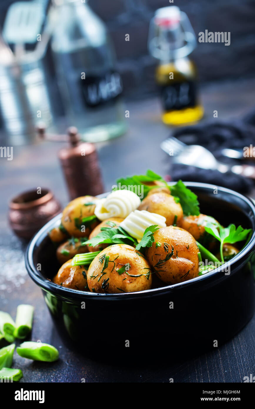 boiled potato with fresh greens and butter - Stock Image