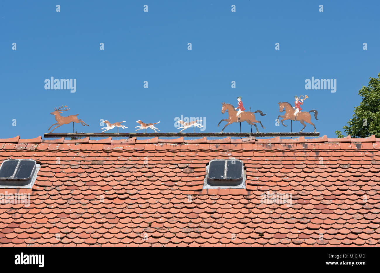 Metal figures hunt scene with hunter, deer and dogs roof of a estate - Stock Image