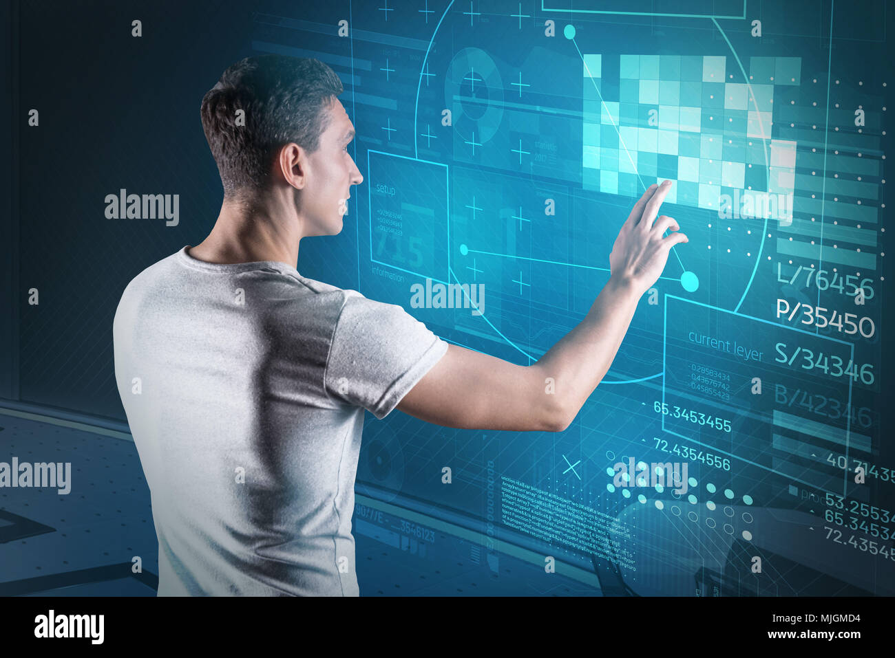 Clever web developer looking interested while working in his office - Stock Image