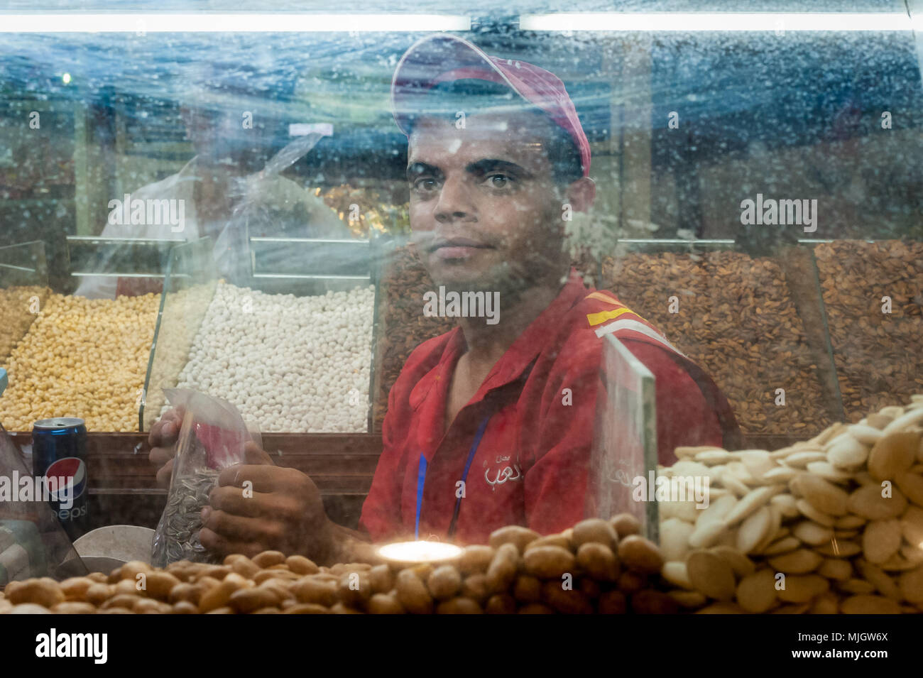 Nuts shopkeeper at Aqaba,al-ʻAqabah, a Jordanian coastal city situated at the northeastern tip of the Red Sea. - Stock Image