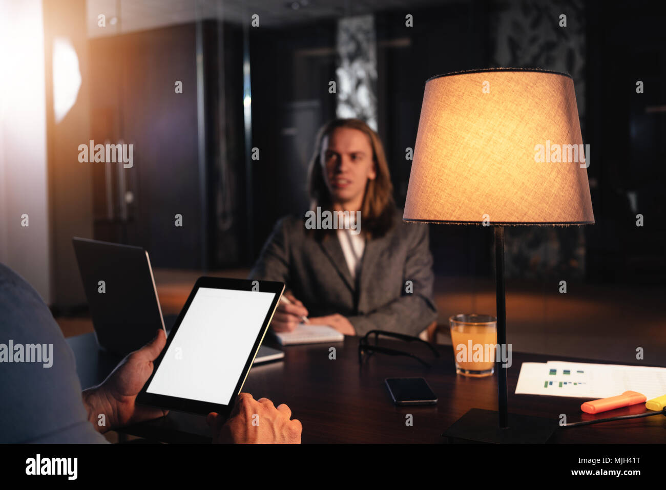 Two coworkers meet in night loft office. Manager conducts an interview. Dialogue of businessmen about a new startup - Stock Image