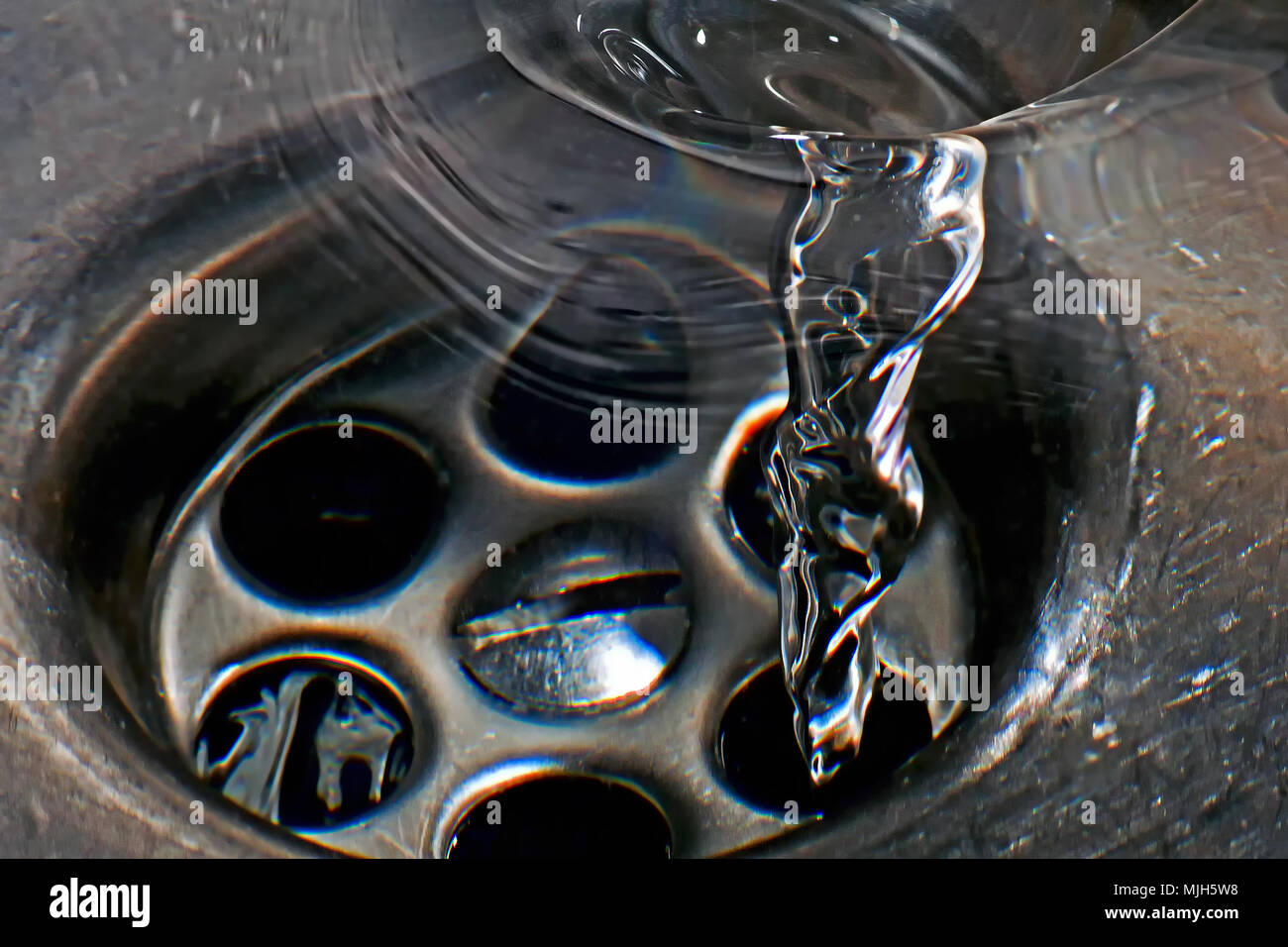 Water spiralling down the plughole in a stainless steel sink. Stock Photo