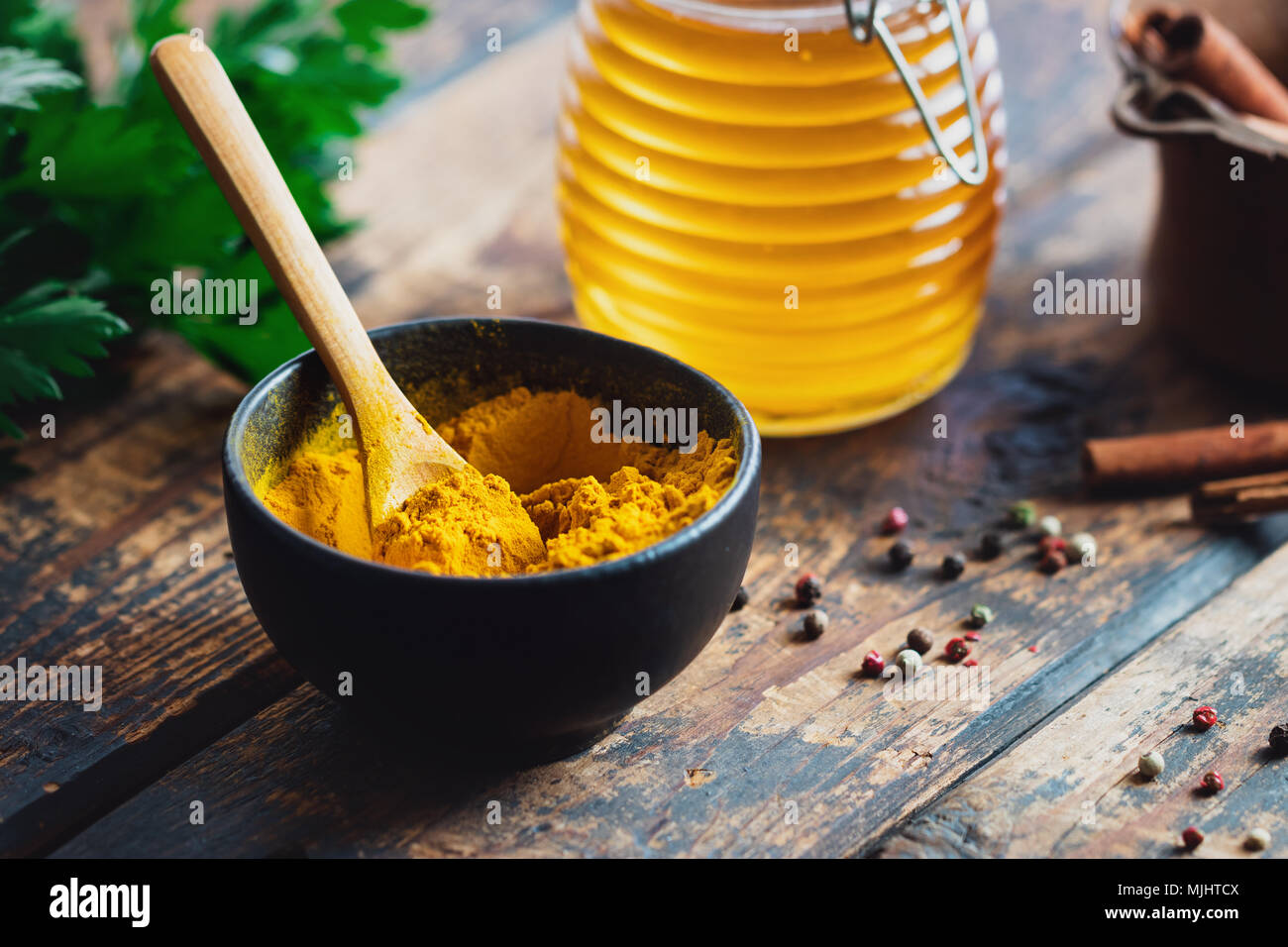 Turmeric powder in a black bowl with spices on rustic wood table - Stock Image