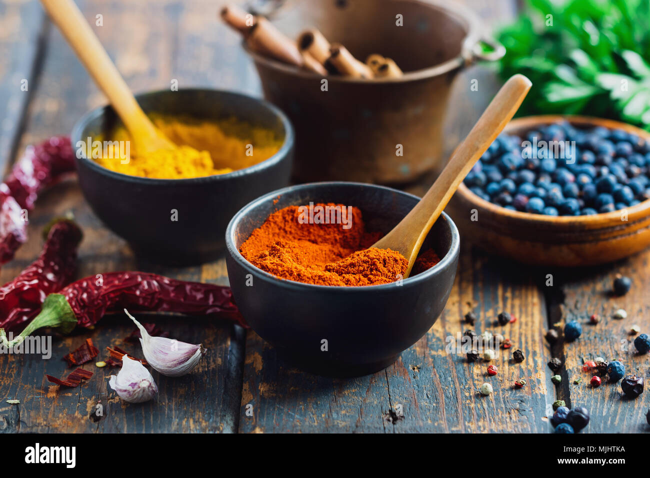 Small bowls filled with spices on rustic wood table. Various ingredients on table. - Stock Image