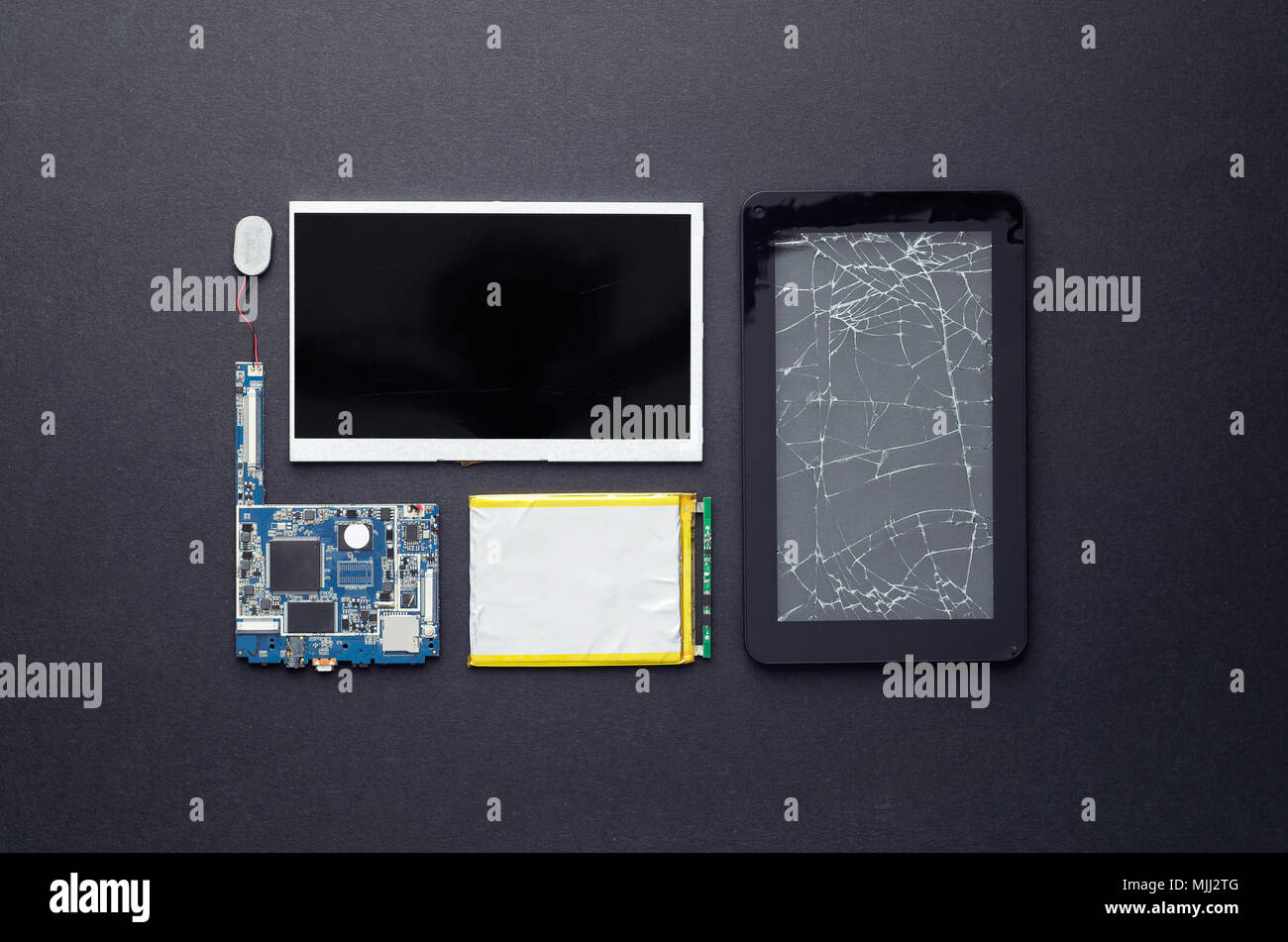Components of a broken tablet organized over black background, top view - Stock Image