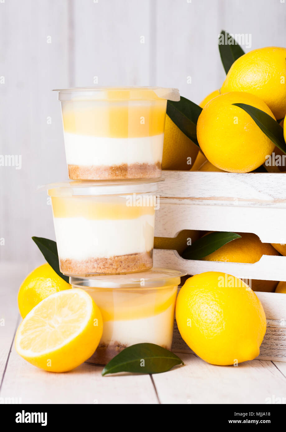 Plastic cup with lemon cream and biscuit dessert with raw lemons in white wooden box Stock Photo