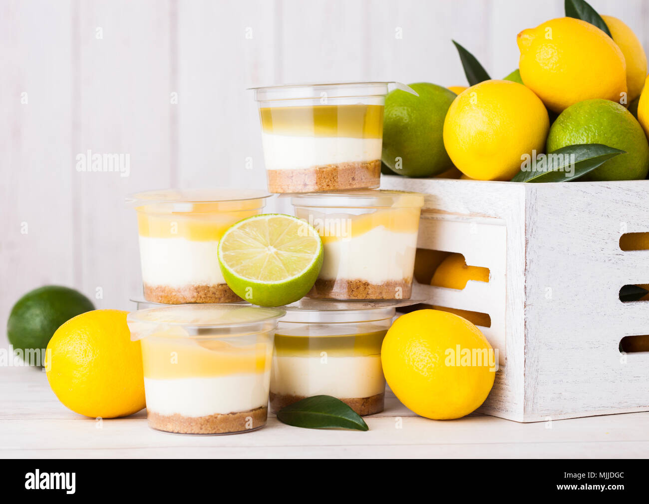 Plastic cup with lemon lime cream and biscuit dessert with raw lemons in white wooden box Stock Photo