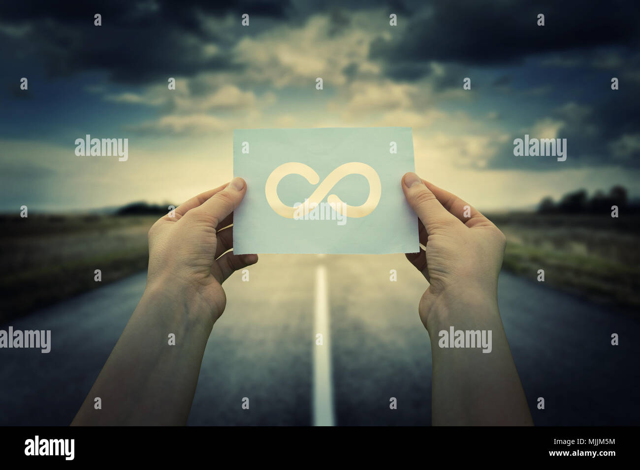 Close up of woman hands holding a paper sheet with infinite sign inside, over endless asphalt road background. The infinity way to nowhere, business c - Stock Image