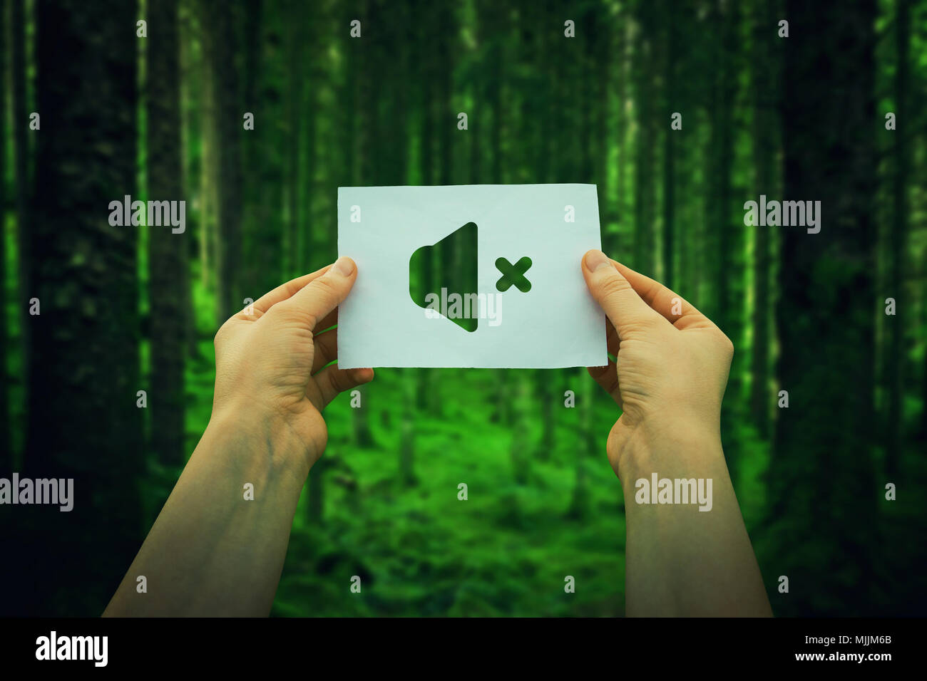 Close up of woman hands holding a paper sheet with silent mode icon, over green forest background. Enjoy the silence of the woods. - Stock Image
