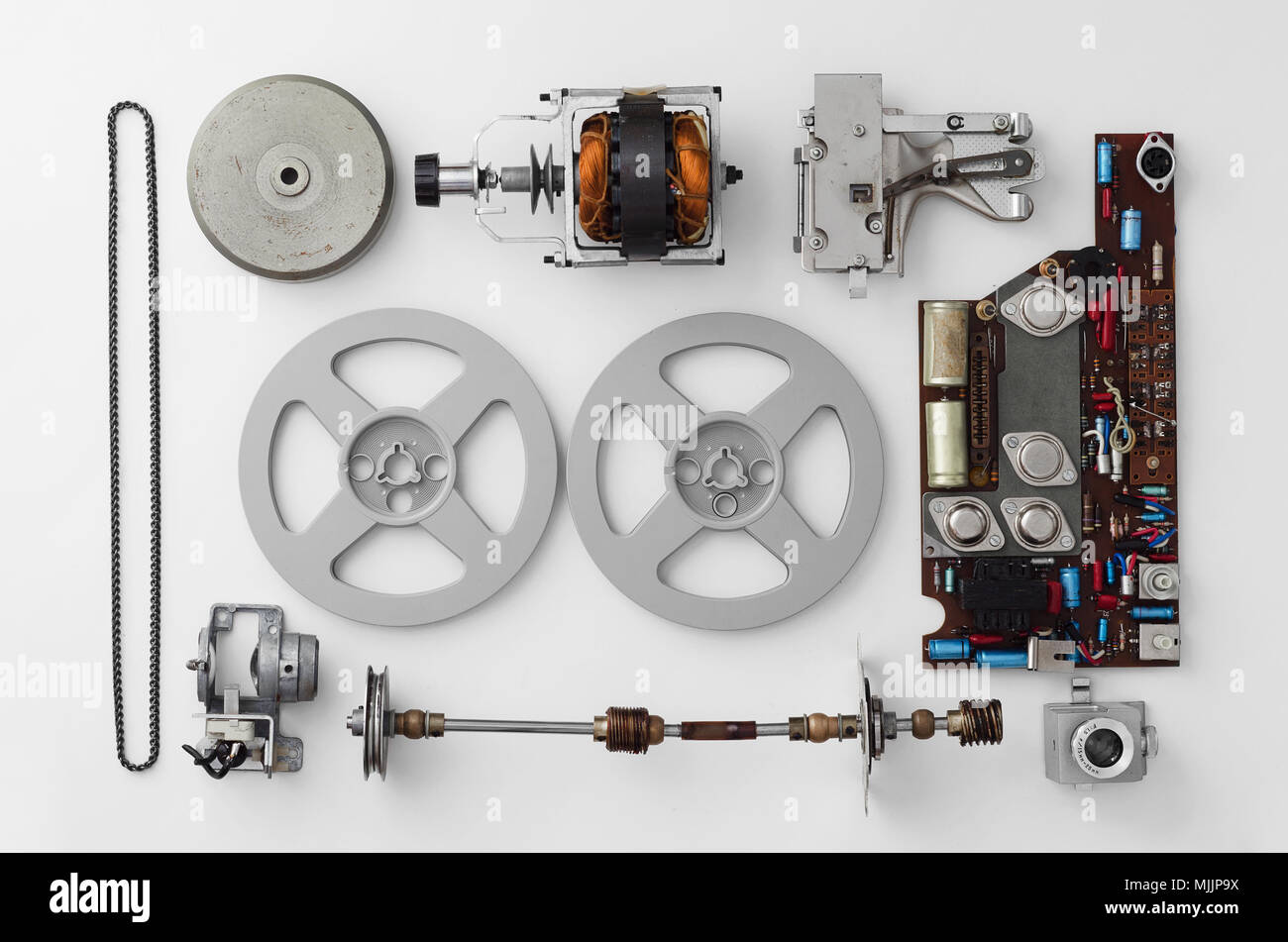 Parts of a vintage film projector well arranged over white background, above view. This is part of a larger series. - Stock Image