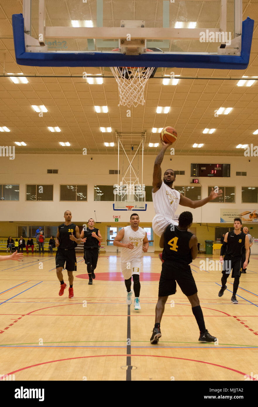171202-F-GF466-1078 SHAPE, Belgium (Dec. 2, 2017) Supreme Headquarters Allied Powers Europe (SHAPE) Basketball Team member Travis Bell attempts a two-point shot around Belgium team member Claudy Bolampete during game 17 of the 2017 SHAPE International Basketball Tournament. The annual event brings together teams from around the world for friendly competition and partnership at a prominent NATO installation.(U.S. Air Force photo by Broadcast Journalist Airman 1st Class Hannah Anderson/Released) Stock Photo