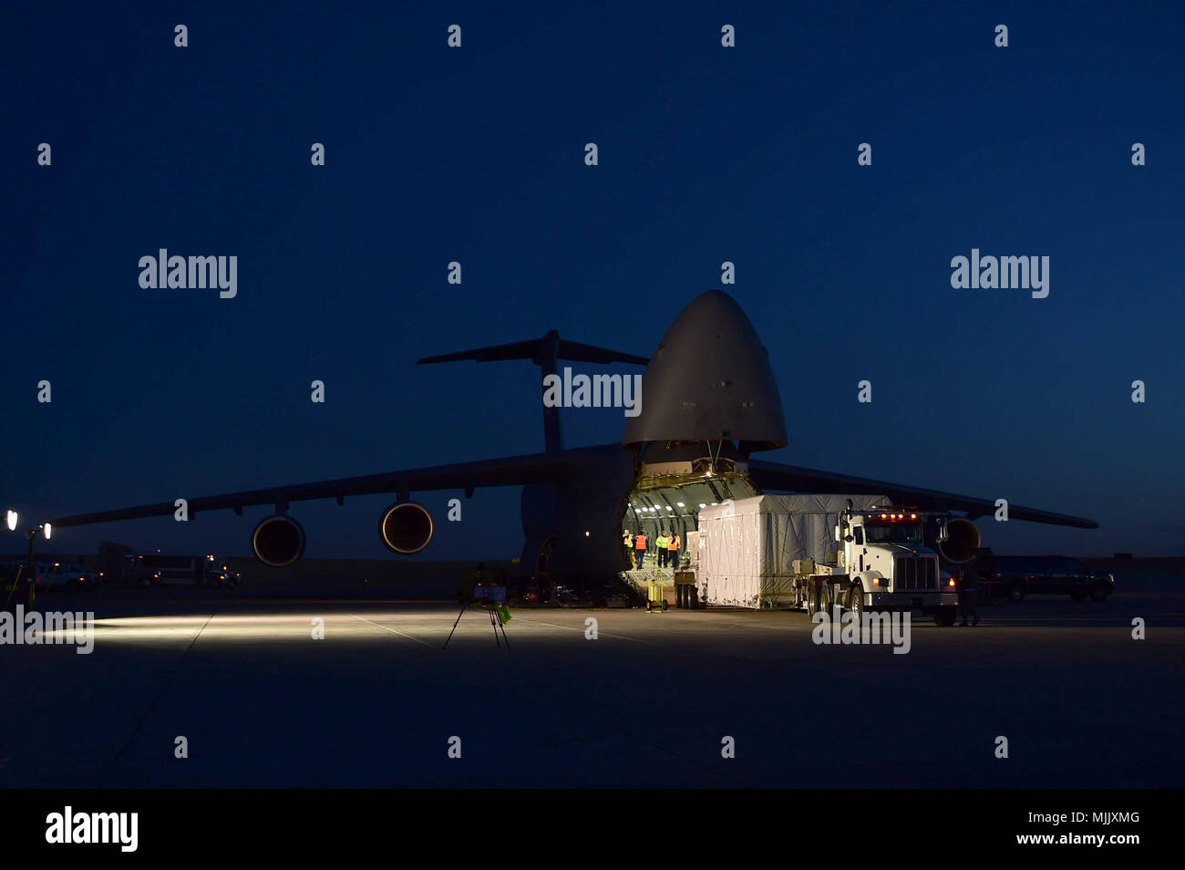 Several units from around the U.S. Air Force alongside members of Lockheed Martin came together to coordinate the loading of the Geostationary Operational Environmental Satellite – R Series into a C-5 Galaxy aircraft Dec. 4, 2017, on Buckley Air Force Base, Colorado. The GOES-R Series will join another satellite currently in orbit to better predict weather patterns and phenomena. The C-5 Galaxy is assigned to Travis AFB, California. (U.S. Air Force photo by Senior Airman Luke W. Nowakowski) - Stock Image
