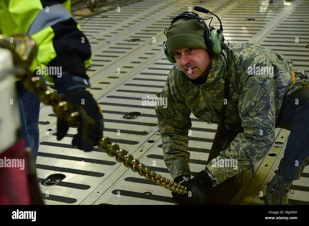 Master Sgt. Jeff Gilbert, 337th Airlift Squadron loadmaster, tightens down a chain connecting the Geostationary Operational Environmental Satellite – R Series to the bed of a C-5 Galaxy aircraft Dec. 4, 2017, on Buckley Air Force Base, Colorado. At more than 100 thousand pounds, it is imperative that the GOES-R Series is correctly fastened to the transport aircraft to ensure safe arrival to Cape Canaveral, Florida. (U.S. Air Force photo by Senior Airman Luke W. Nowakowski) - Stock Image