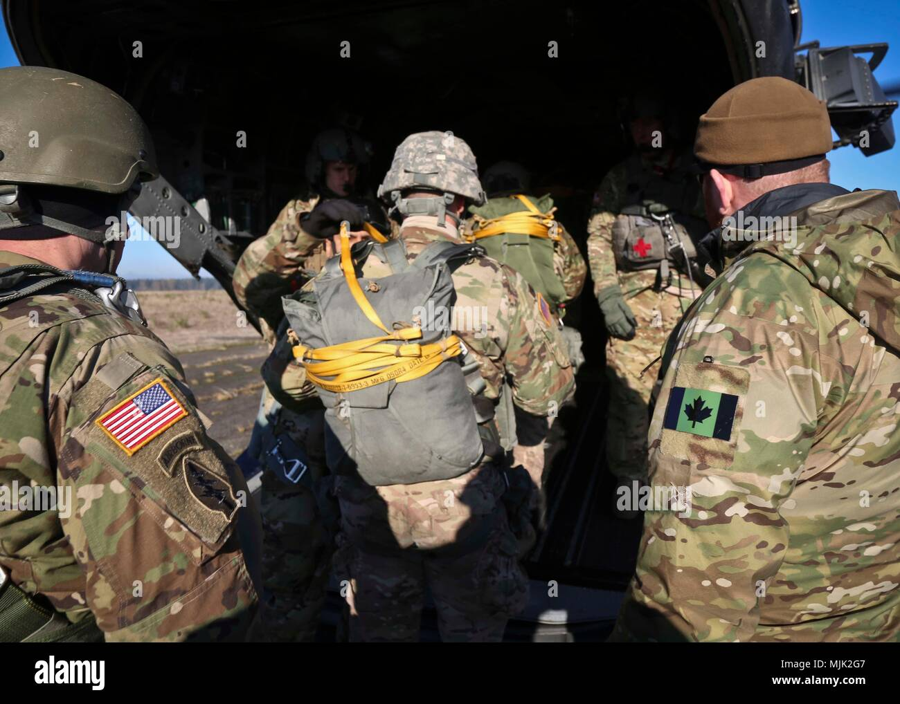 Members of the 1st Special Forces Group (Airborne) conduct an Airborne operation with the Canadian Special Operations Regiment (CSOR) during Menton week at Joint Base Lewis-McChord, Wa., Dec 6, 2017. After the jump, Soldiers from 1SFG (A), Filipino and Canadian paratroopers conducted a ceremony where they exchanged their countries' jump wings with one another. Stock Photo