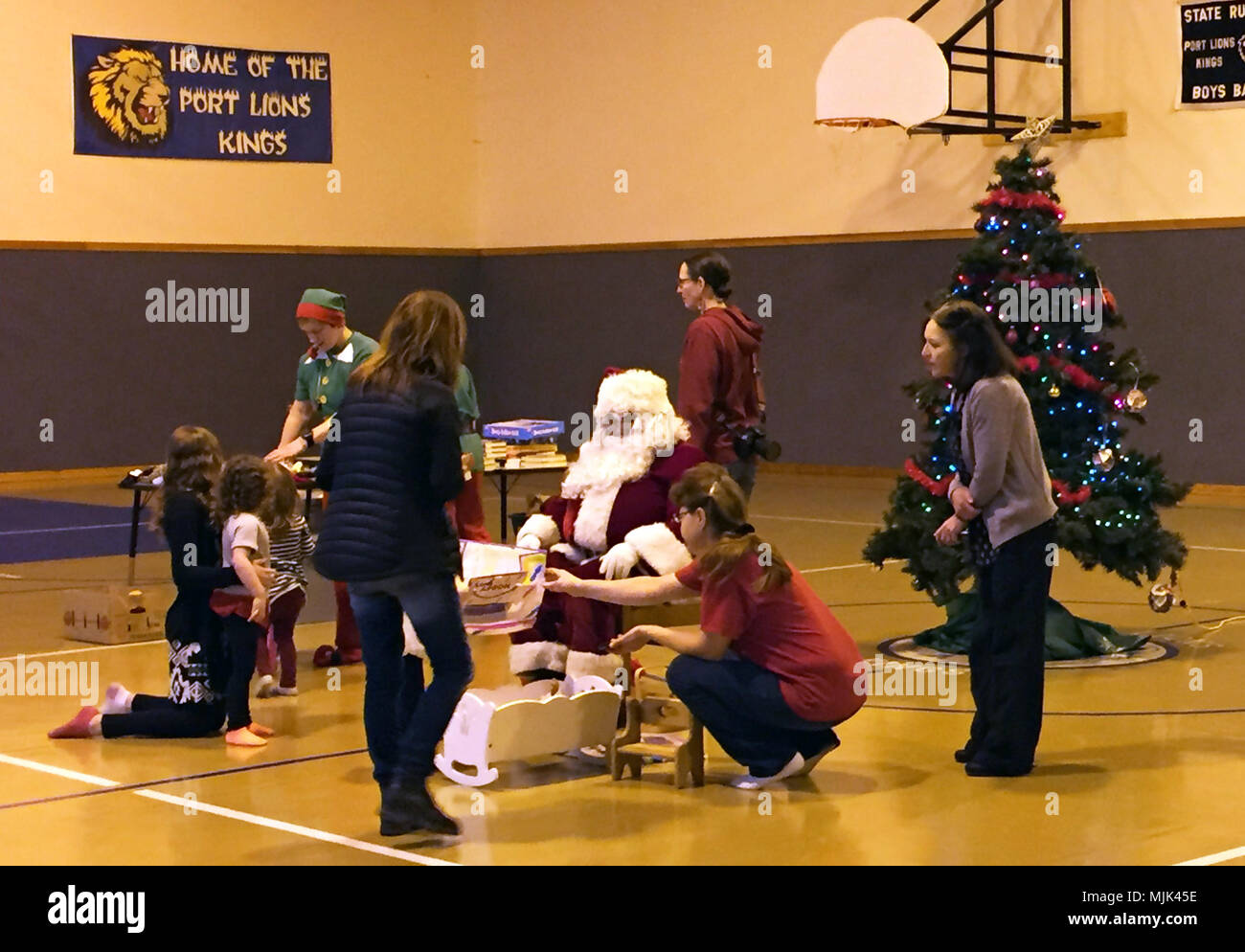 santa claus teachers and parents help with handing out christmas presents to the port lions children at the the port lions public school gym in port lions