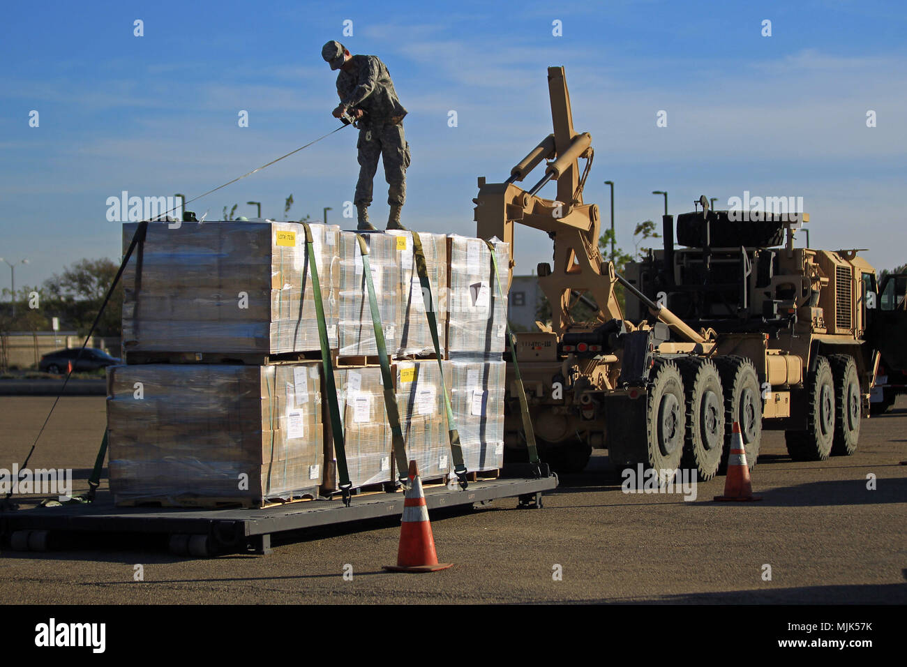 U.S. Army National Guard Private 1st Class Kane Coronado of the 756th Transportation Company in Lancaster, California, secures pallets of food onto a palletized loading system Thurs., Dec. 7, 2017, at Joint Forces Training Base Los Alamitos, California. The base is being used as a multiagency staging area in support of wildfire response efforts in Southern California as fires continue to burn in the region. (U.S. Air National Guard photo by Senior Airman Crystal Housman) Stock Photo