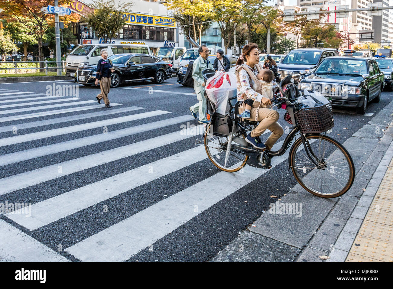 Mother with child cycling in Osaka Japan - Stock Image