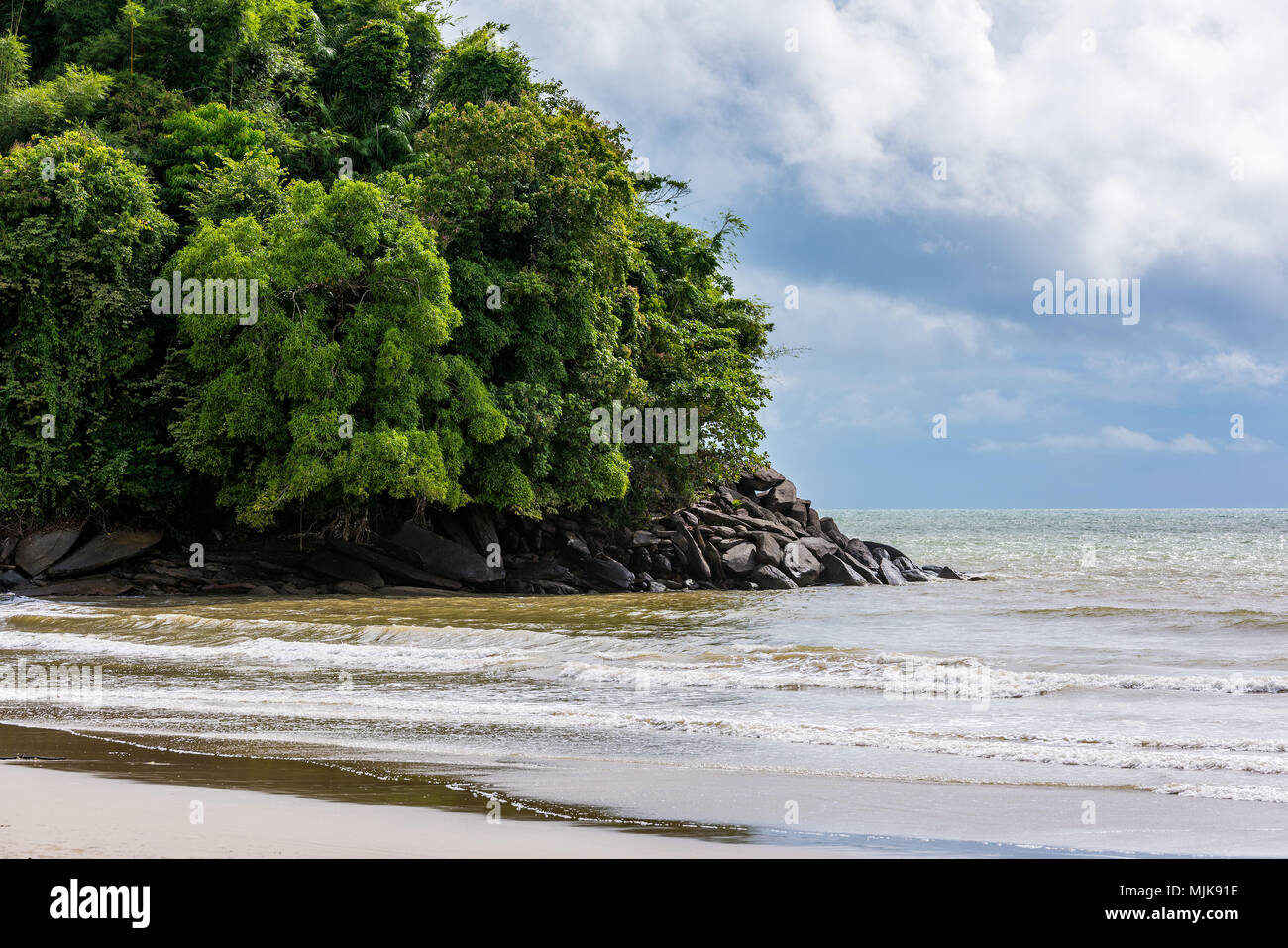 The beach has rocky outcrops in the sea. - Stock Image