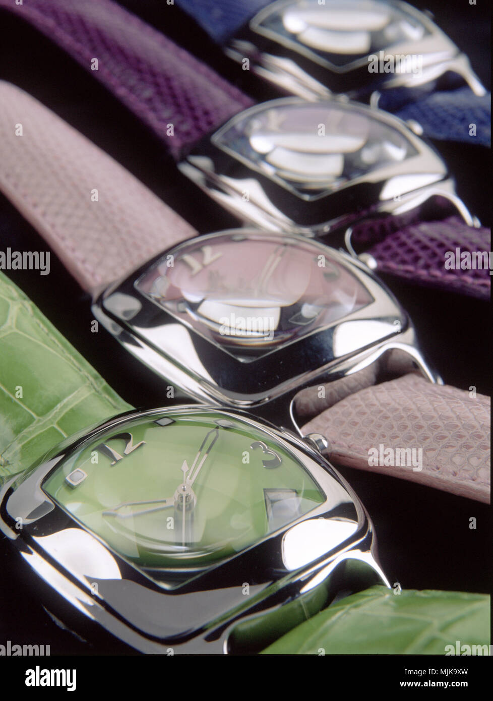 Closeup of set of colorful wristwatches on black background - Stock Image