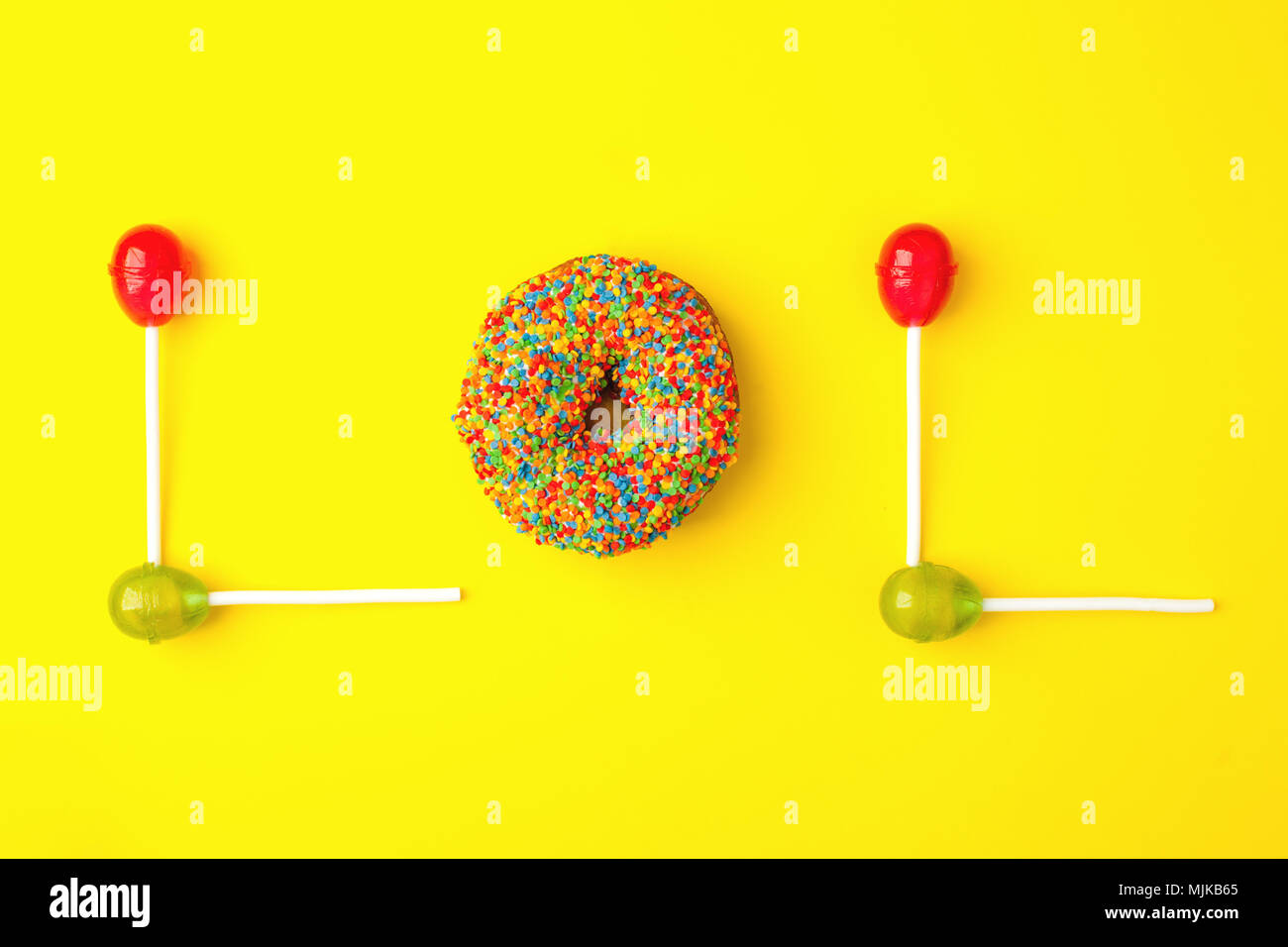 Word lol from sweetness on yellow background. Abbreviation stands for laugh out loud, flat lay trendy background - Stock Image