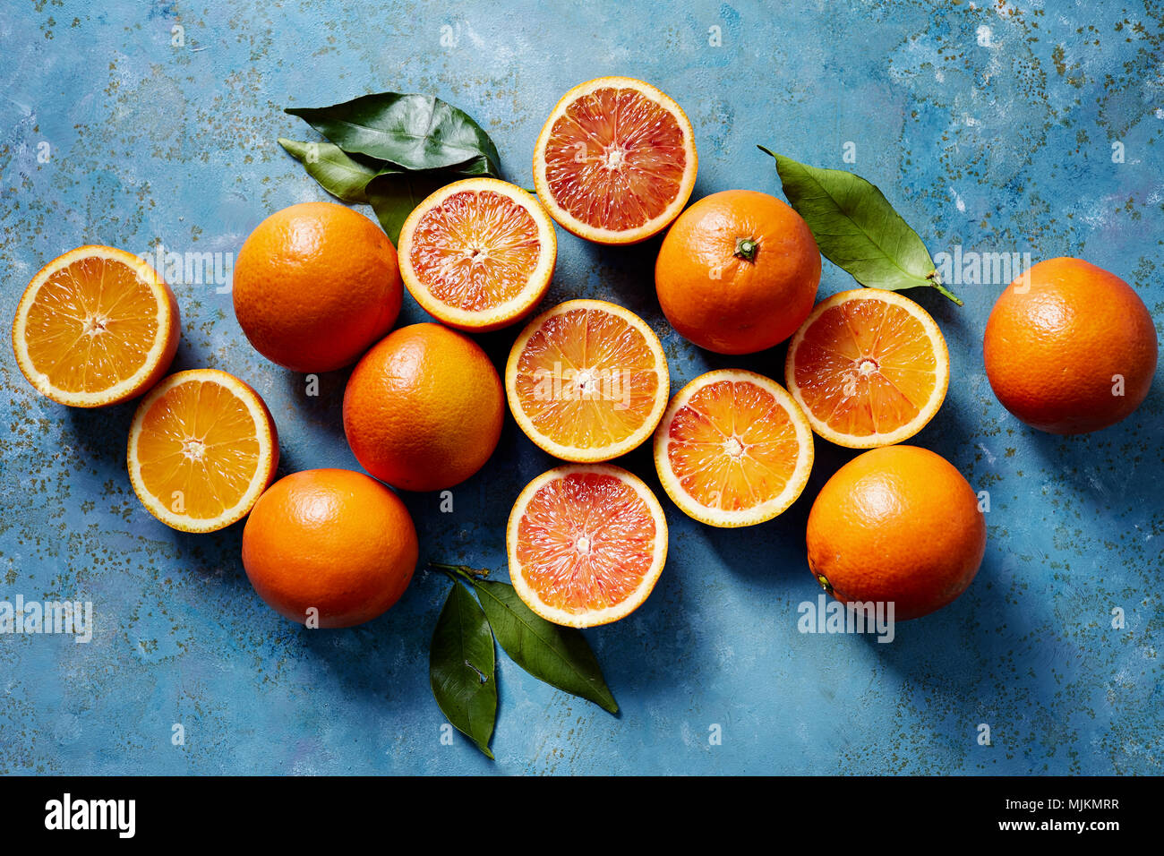 Blood oranges whole and sliced on a blue surface (seen from above). - Stock Image