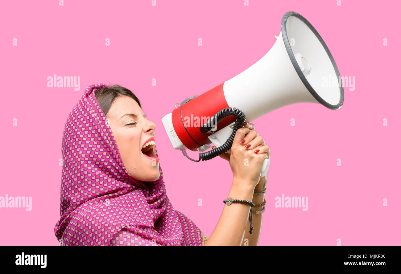 Young arab woman wearing hijab communicates shouting loud holding a megaphone, expressing success and positive concept, idea for marketing or sales - Stock Image