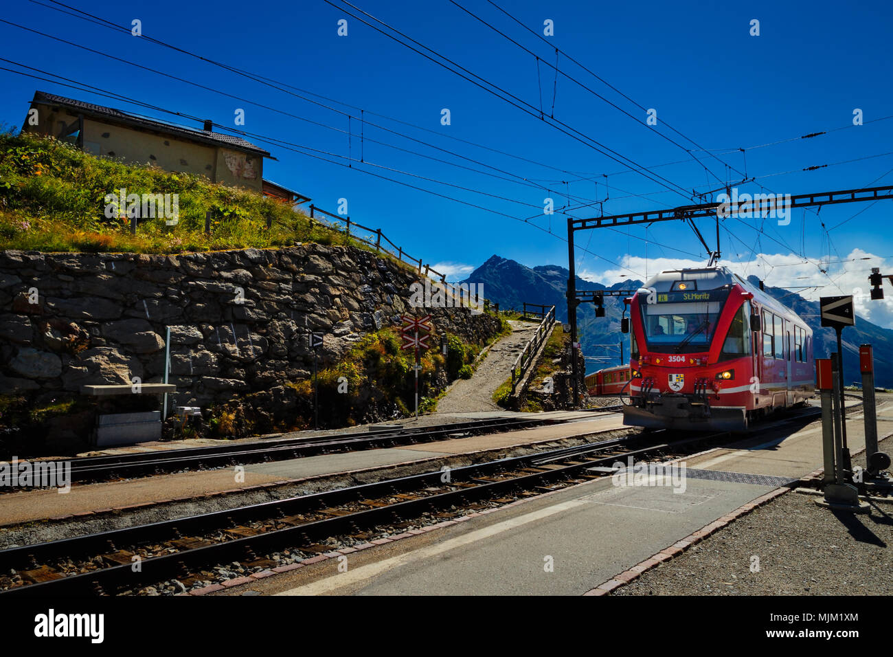 Poschiavo, Grisons, Switzerland - AUGUST 10, 2016 : red train of the Rhaetian Railway entering the station Alp Grum on a sunny day in summer - Stock Image