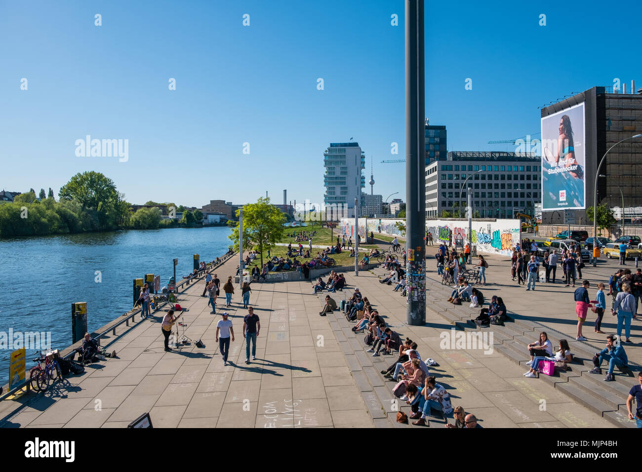 Berlin, Germany - may, 2018:  Many people at river Spree at Berlin Wall ( East Side Gallery) on a sunny day in Berlin, Germany Stock Photo