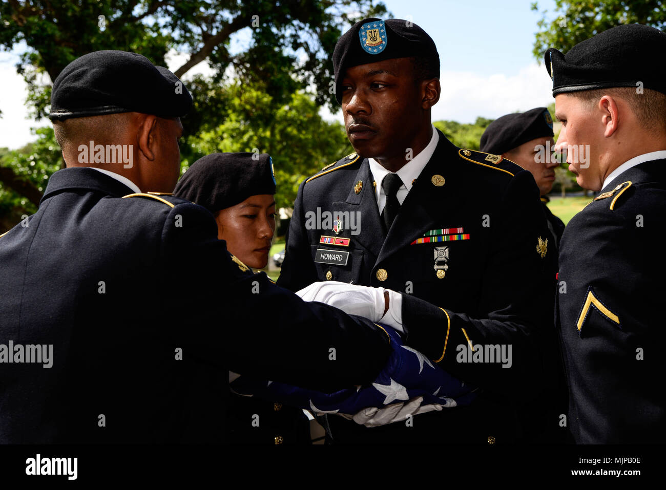 U.S. Soldiers assigned to 225th Brigade Support Battalion, 2nd Infantry Brigade Combat Team, 25th Infantry Division fold the burial flag of U.S. Army Pfc. Albert E. Atkins, Dec. 15, 2017, at the National Memorial Cemetery of the Pacific, Honolulu, Hawaii. On May 23, 1951, Atkins, a member of Company E, 2nd Battalion, 187th Airborne Infantry Regiment, 187th Airborne Regimental Combat Team, engaged enemy forces with his unit near Mae-Bong, South Korea. Atkins and two other soldiers from his company were reported missing in action. Atkins was recently identified through DNA analysis with the help - Stock Image