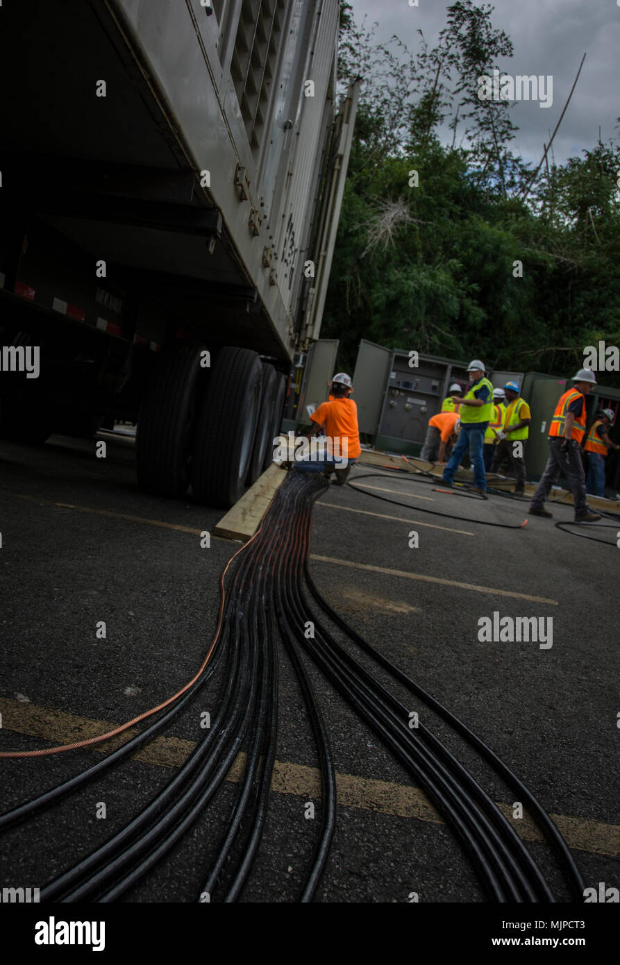 Contractors work to install a micro grid in Patillas on Dec. 17, 2017. The micro grid concept brings approximately 5 megawatts of power directly into the existing infrastructure in the area, bringing electricity to nearby buildings. The concept is significant in that it is a temporary power mission – usually intended to support critical infrastructure during an emergency – bringing electricity to residents and businesses. The installation – the second micro grid installed on the island – will be operational by midweek, with the third set to open in nearby Maunabo shortly after. - Stock Image
