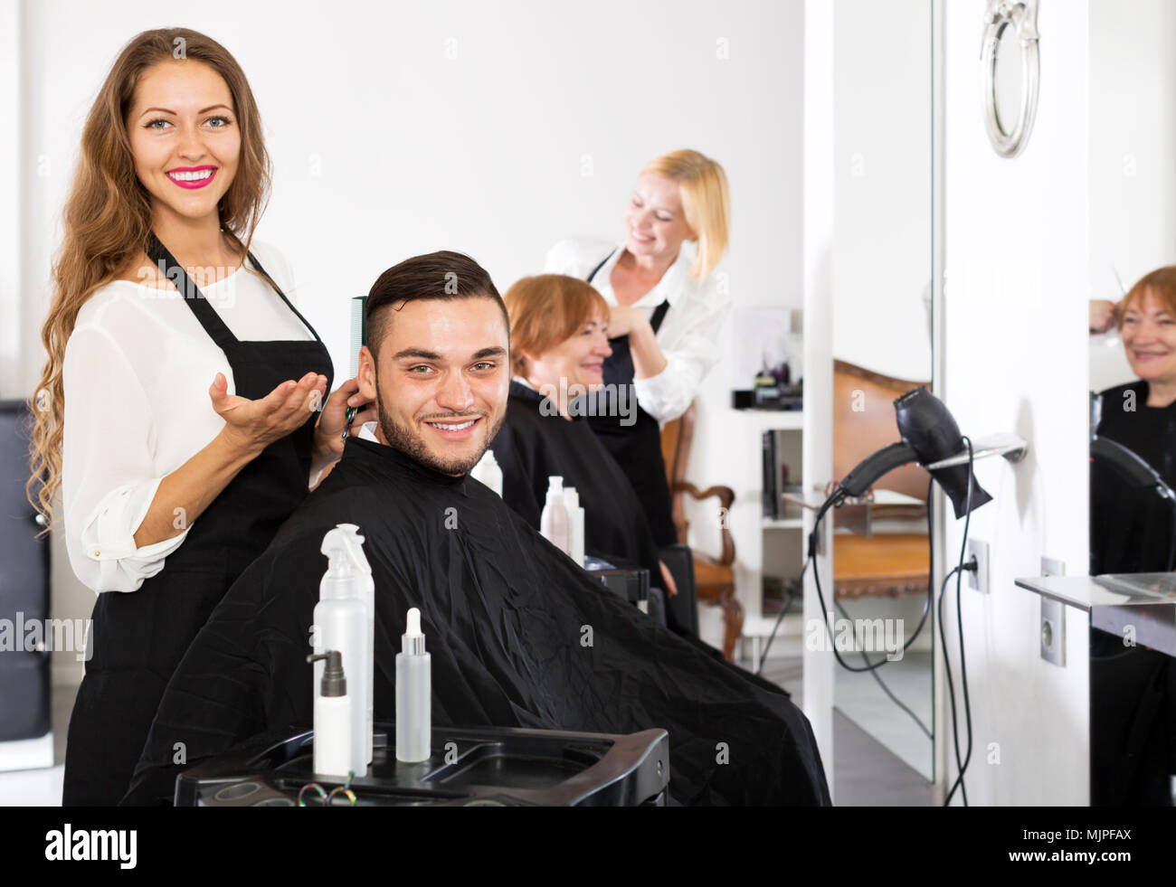 Happy young guy cuts hair at the hair salon Stock Photo - Alamy