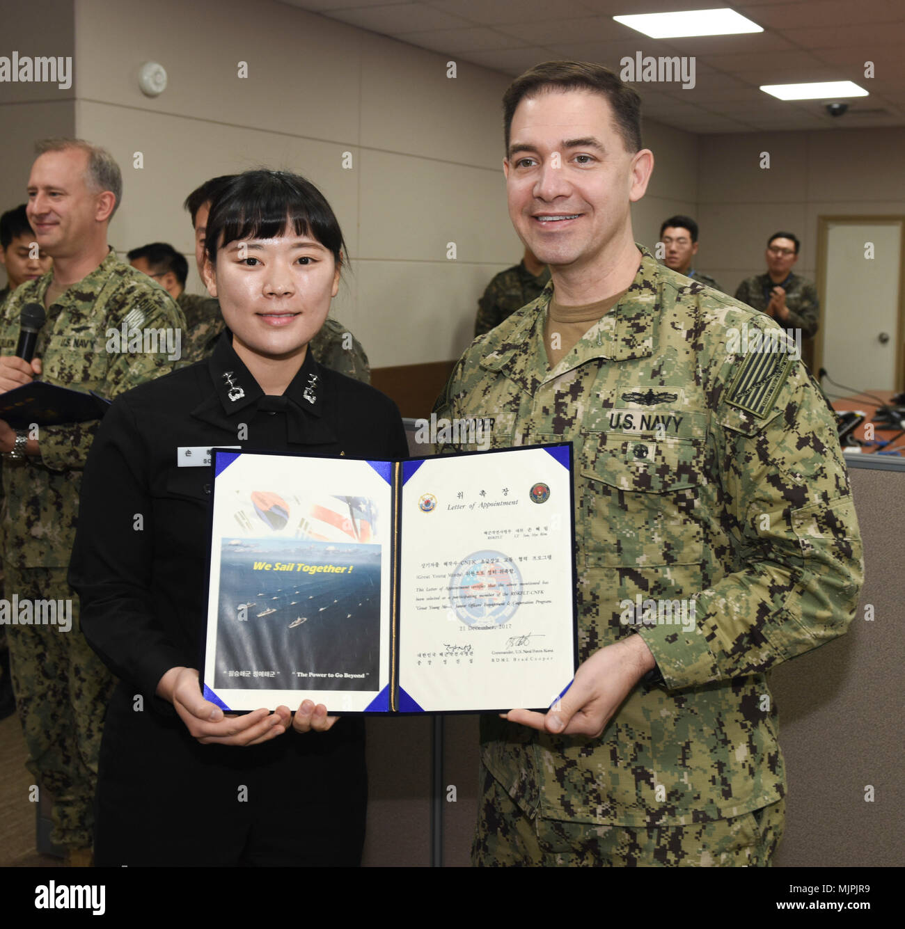 "171221-N-TB148-056 BUSAN, Republic of Korea (Dec. 21, 2017) Rear Adm. Brad Cooper, commander, U.S. Naval Forces Korea (CNFK), presents Lt. Son, Hye Rim with a letter of appointment for her selection to the ""Great Young Minds"" Junior Officers' Engagement and Cooperation Program. The ""Great Young Minds"" initiative brings together hand-selected, young officers from the ROK and U.S. navies and challenges them to develop innovative solutions to further enhance the ROK -U.S. alliance of the future. (U.S. Navy photo by Mass Communication Specialist Seaman William Carlisle) Stock Photo"
