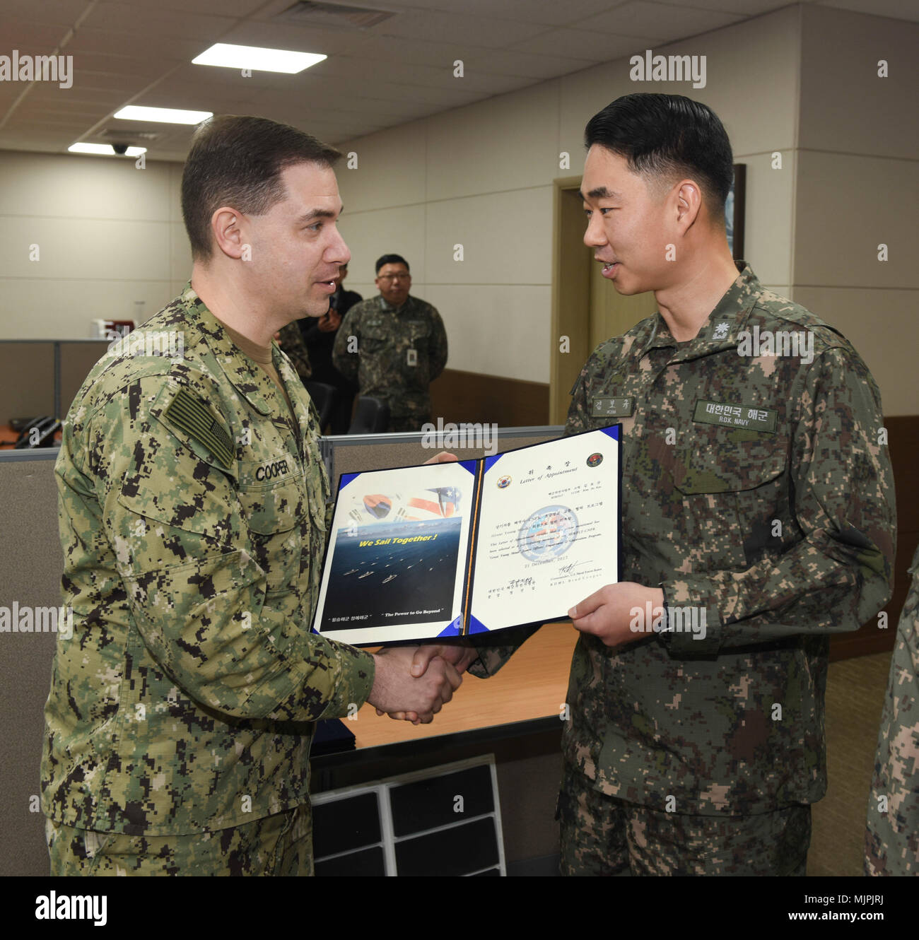 """171221-N-TB148-025 BUSAN, Republic of Korea (Dec. 21, 2017) Rear Adm. Brad Cooper, commander, U.S. Naval Forces Korea (CNFK), presents Lt. Cmdr. Kim, Bo Kyu with a letter of appointment for her selection to the """"Great Young Minds"""" Junior Officers' Engagement and Cooperation Program. The """"Great Young Minds"""" initiative brings together hand-selected, young officers from the ROK and U.S. navies and challenges them to develop innovative solutions to further enhance the ROK -U.S. alliance of the future. (U.S. Navy photo by Mass Communication Specialist Seaman William Carlisle) Stock Photo"""