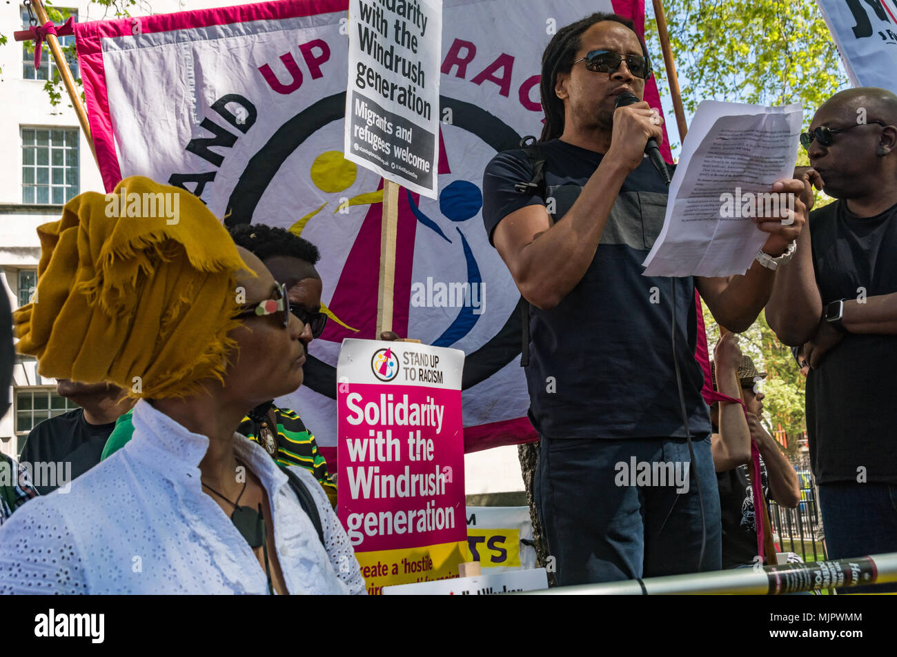 London, UK. 5th May 2018. A speaker at the Stand Up To Racism rally at Downing St calling for Theresa May's racist 2014 Immigration Act to be repealed and an immediate end to the deportation and detention of Commonwealth citizens, with those already deported to be bought back to the UK. The protesters called for protection to the guaranteed for all Commonwealth citizens and for those affected to be compensated for deportation, threats of deportation, detention, loss of housing, jobs, benefits and denial of NHS treatment. There should be an end to the 'hostile environment' for all immigrants. S Stock Photo