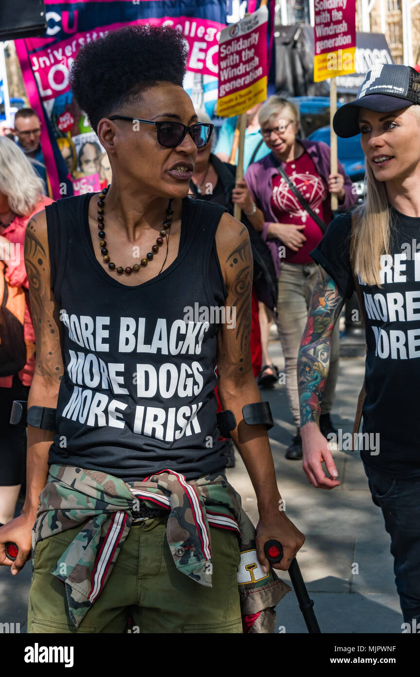 London, UK. 5th May 2018. A woman wearing a t-shirt 'More Blacks More Dogs More Irish' marches with the help of crutches from Downing St for a protest outside the Home Office calling for Theresa May's racist 2014 Immigration Act to be repealed and an immediate end to the deportation and detention of Commonwealth citizens, with those already deported to be bought back to the UK. They called for protection to the guaranteed for all Commonwealth citizens and for those affected to be compensated for deportation, threats of deportation, detention, loss of housing, jobs, benefits and denial of NHS t Stock Photo