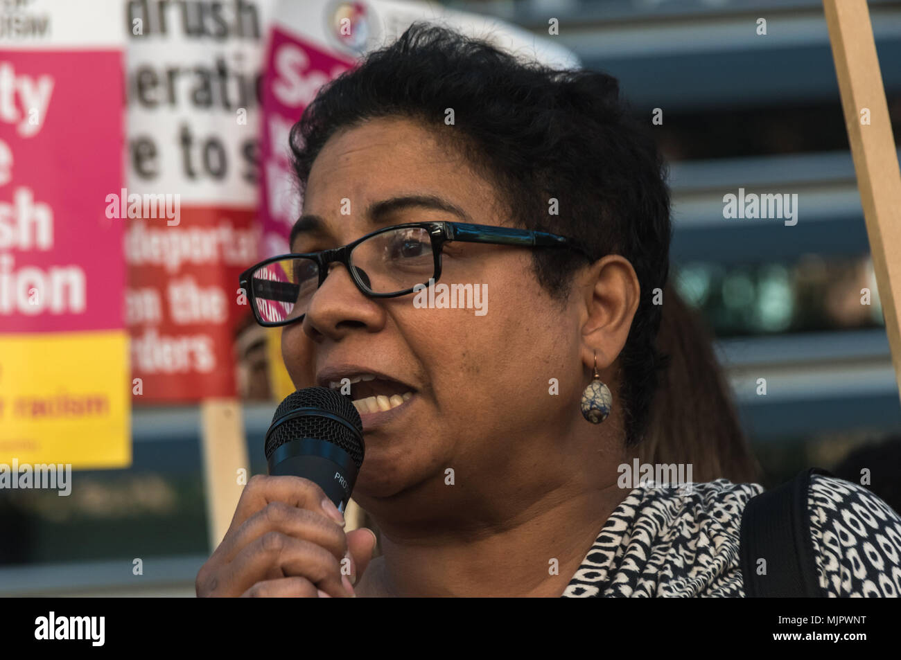 London, UK. 5th May 2018. An immigration lawyer reads a poem she has written about the Windrush experience of arriving in cold damp England and experiencing raciism at the protest outside the Home Office calling for Theresa May's racist 2014 Immigration Act to be repealed and an immediate end to the deportation and detention of Commonwealth citizens, with those already deported to be bought back to the UK. They called for protection to the guaranteed for all Commonwealth citizens and for those affected to be compensated for deportation, threats of deportation, detention, loss of housing, jobs,Stock Photo
