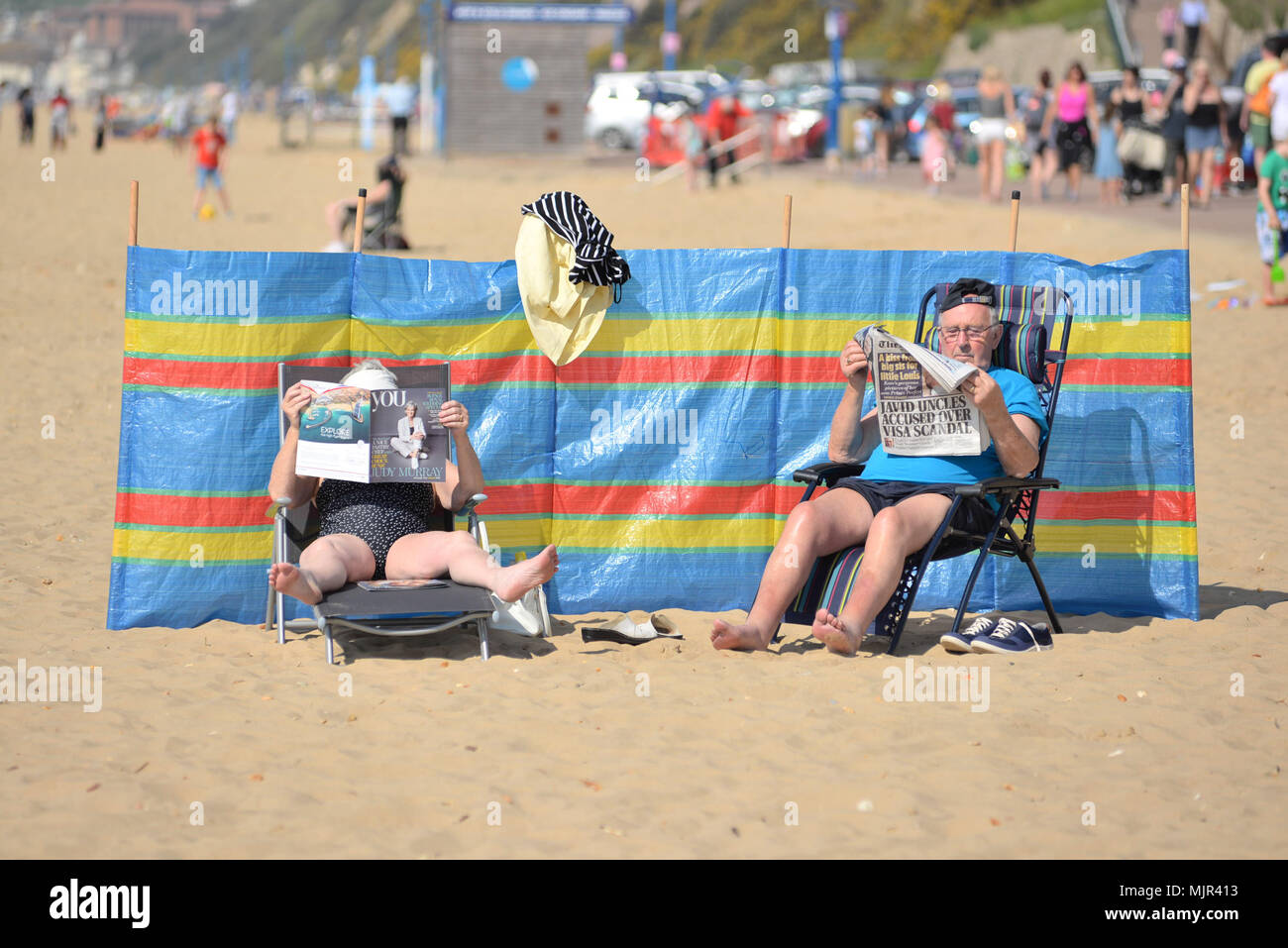 Boscombe, Bournemouth, Dorset, UK, 6th May 2018: Couple sitting on chairs with their feet up reading newspapers and relaxing on the beach in hot sunshine protected by a wind break. Hottest Mayday bank holiday weekend on record. Alamy News - Stock Image