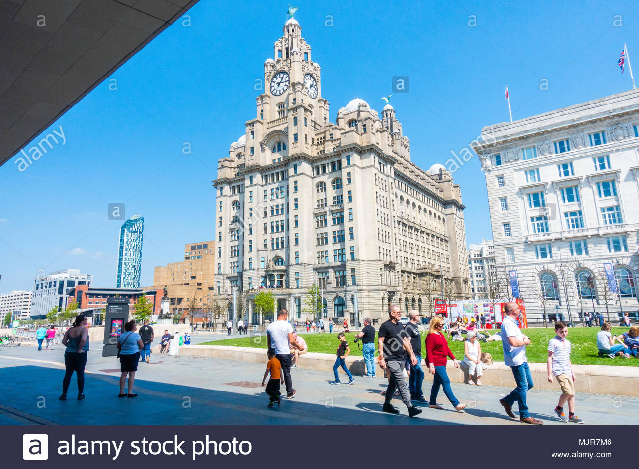 Glorious sunshine at the Pier Head on the banks of the River Mersey, people walking in the sunshine in front of the Liver Building, on a sunny Bank Holiday Weekend, Liverpool, England UK Europe Stock Photo