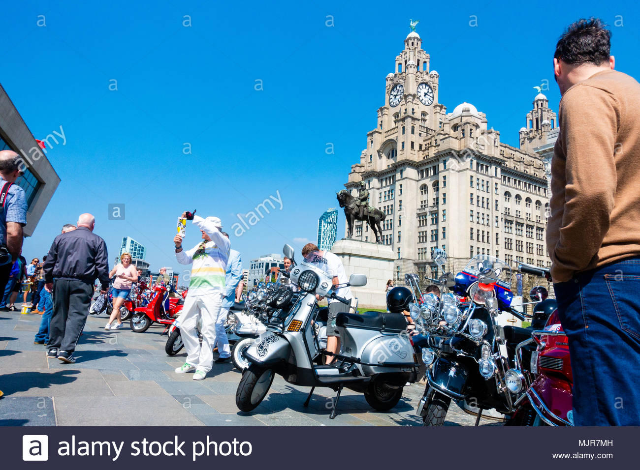 Mods and scooters at the Pier Head on the banks of the River Mersey, people gather in front of a load of mods with scooters in the sunshine in front of the Liver Building, on a sunny Bank Holiday Weekend, Liverpool, England UK Europe Stock Photo