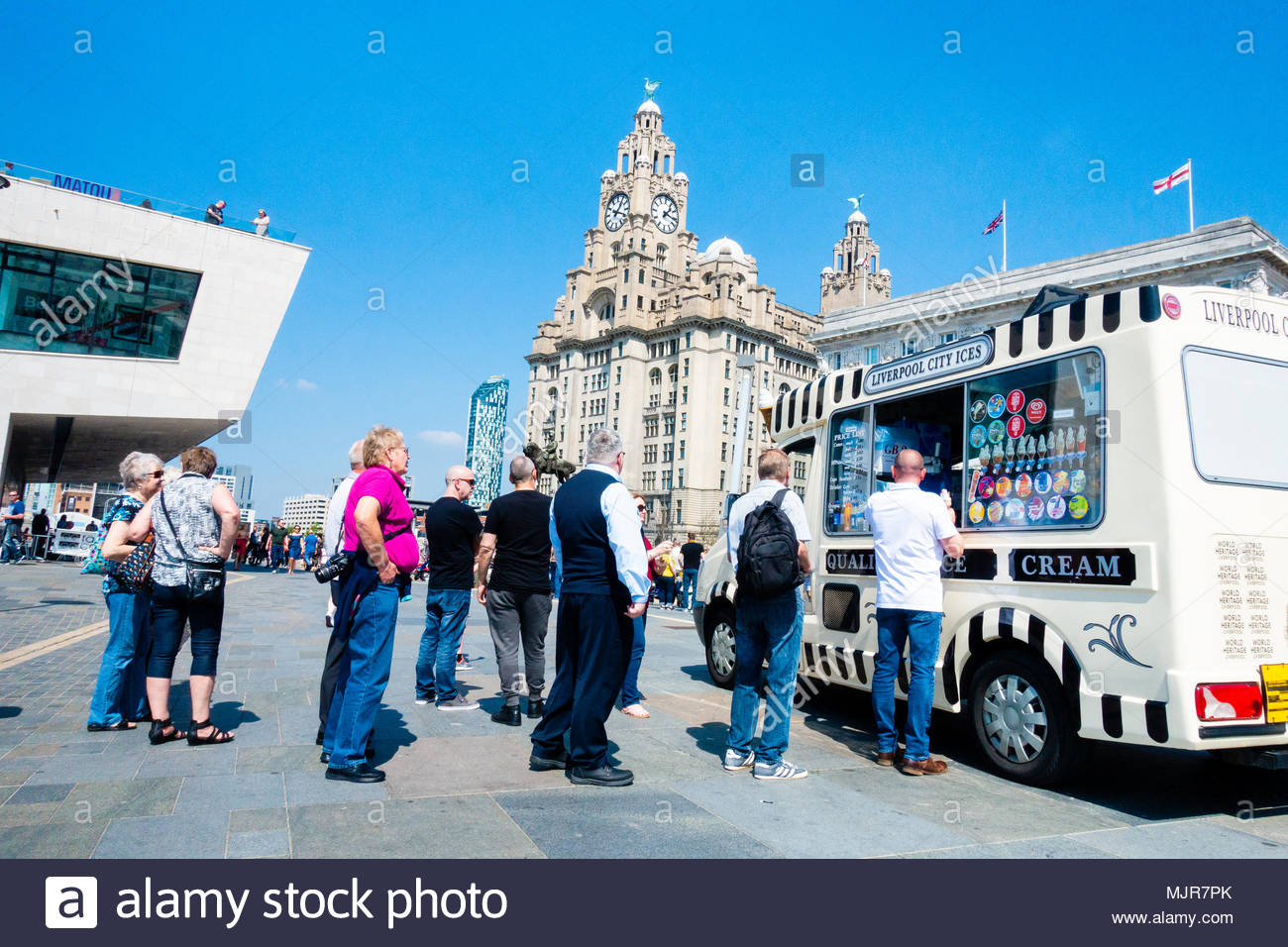 Pier Head in Liverpool, on the banks of the River Mersey, people queue to buy an Ice Cream to col down on the unusually hot day, in front of the Liver Building, on a sunny Bank Holiday Weekend, Liverpool, England UK Europe Stock Photo