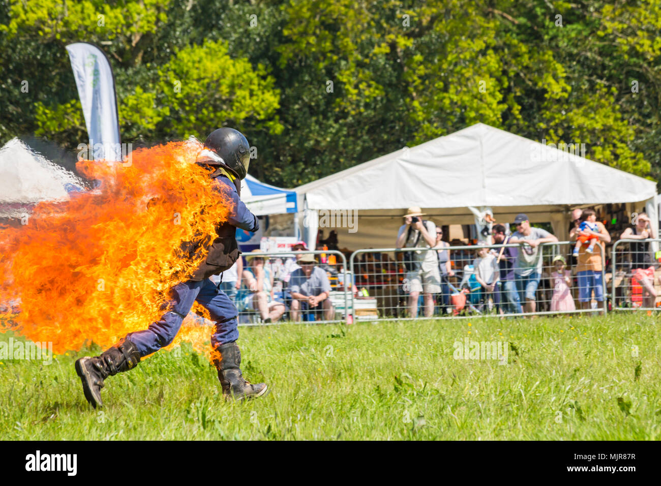 Netley Marsh, Hampshire, UK. 6th May 2018. The first day, of the two day event, Hampshire Game & Country Fair attracts the crowds on a hot sunny day. Stannage International Stunt Display Team thrill the crowds as a stuntman runs around the arena on fire. Credit: Carolyn Jenkins/Alamy Live News - Stock Image