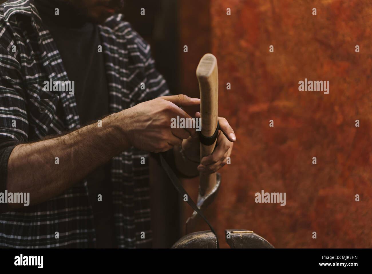 Man working in carpentry workshop. He wraps leather with wooden handle ax. Men at work. Hand work. - Stock Image