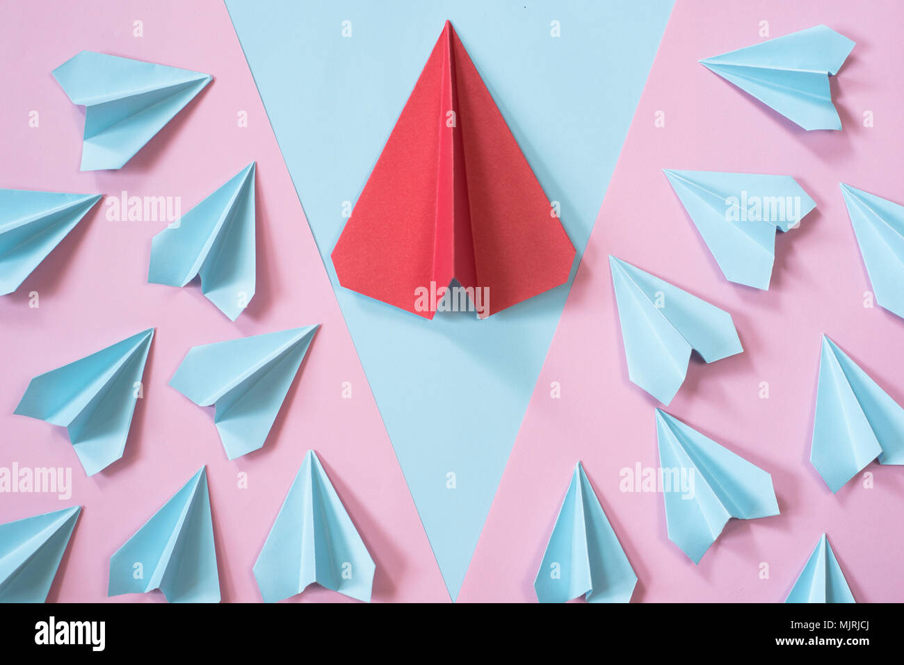 blue paper airplanes surrounding the bigger red paper airplane on pastel pink and blue color background. leadership concept - Stock Image