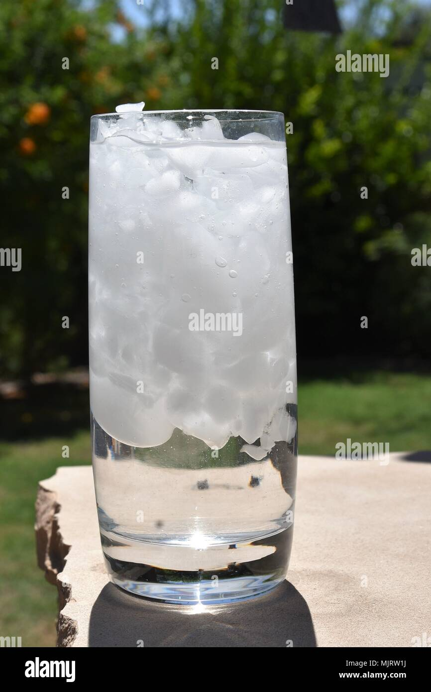 Cold glass of ice water on a hot day - Stock Image