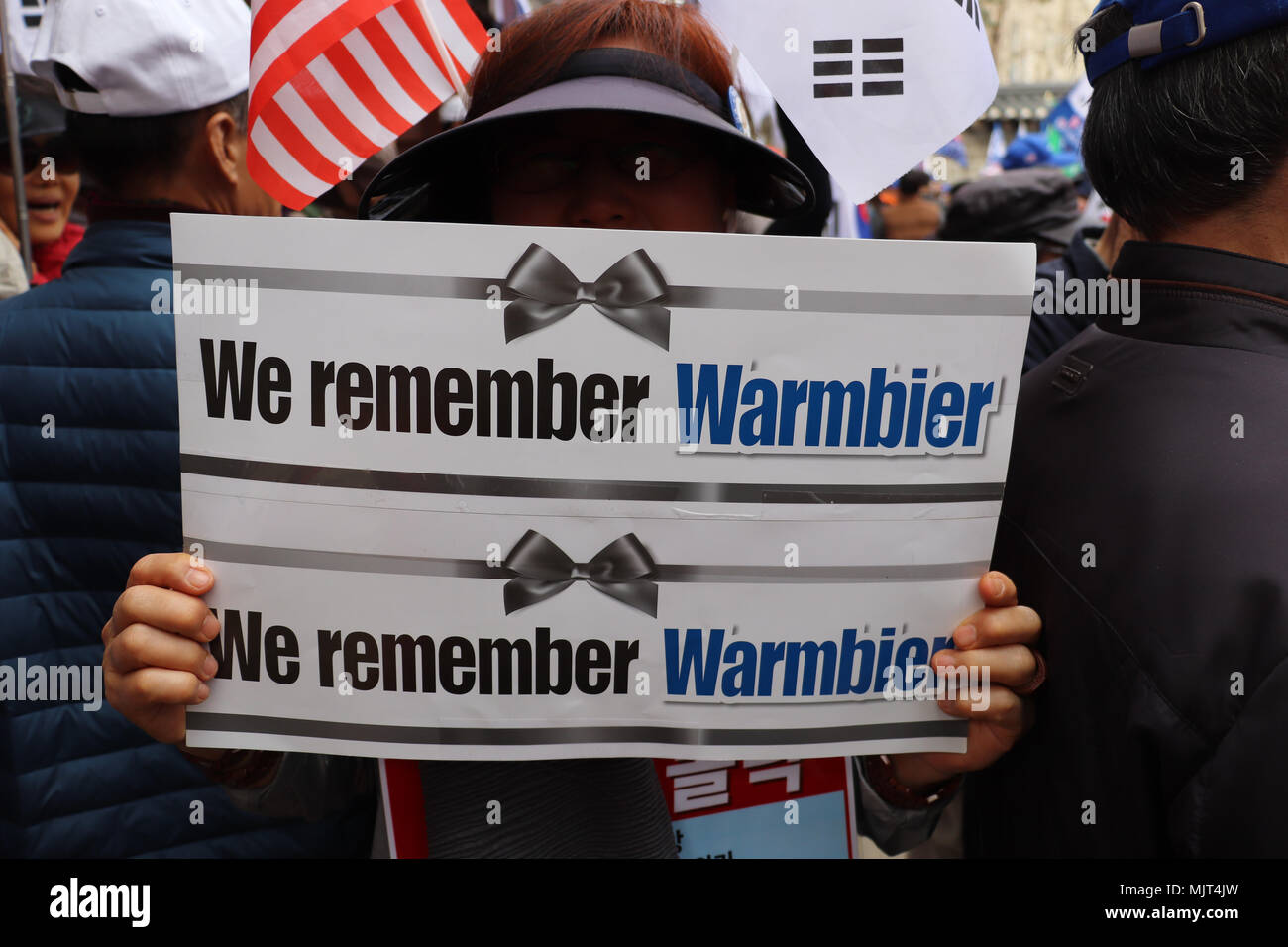 Woman holds a 'We remember Warmbier' sign at a political rally in Seoul, South Korea on March 31, 2018, with US flag in background, for unification. - Stock Image