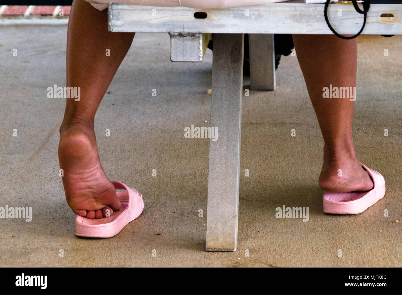 ac76be3b5b4bed A woman relaxing on a bench at a park inadvertently showing off dirty feet  in plastic