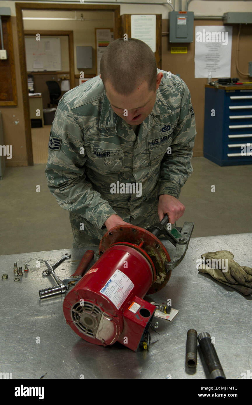 U.S. Air Force Staff Sgt. Matthew Auger, a 354th Civil Engineer Squadron heating, ventilation, and air conditioning technician, repairs a leaking glycol pump Dec. 27, 2017, at Eielson Air Force Base, Alaska. The pump, which is essential to the building's heating system, required a new seal to stop the leak and return to normal function. (U.S. Air Force photo by Airman 1st Class Eric M. Fisher) - Stock Image
