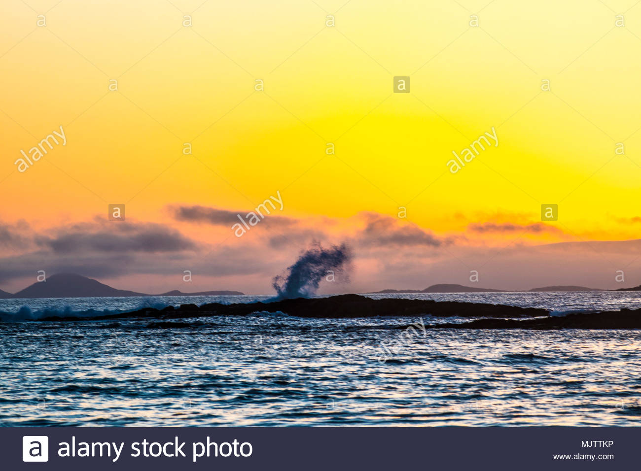 Surf spray in Coulagh Bay with sun setting over the Kerry peninsula in the background - Stock Image