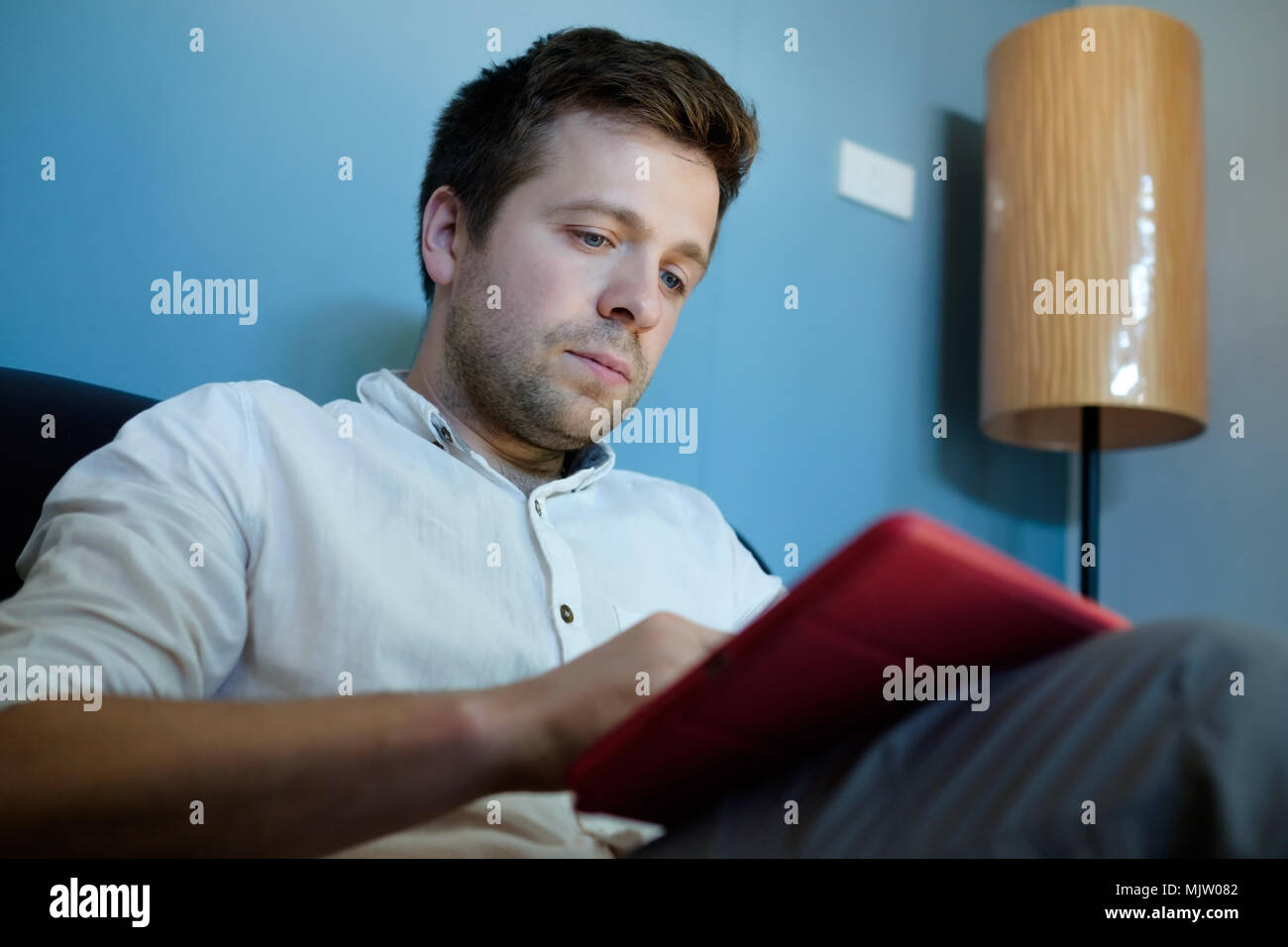 Handsome caucasian man in white shirt using his tablet sitting on a couch Stock Photo