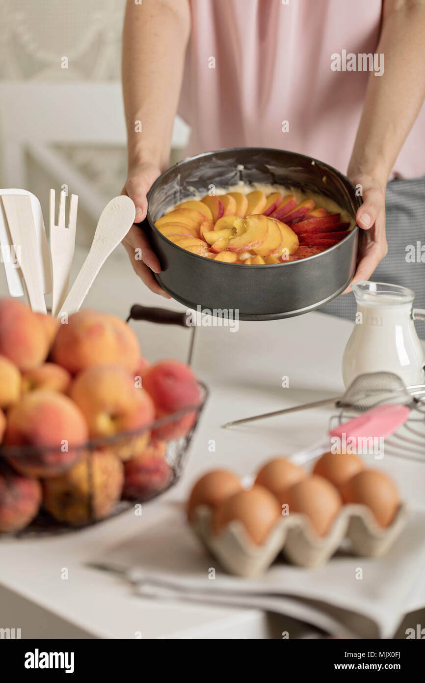 Preparation of homemade peach pie kitchen accessories and products female hands in the frame selective focus